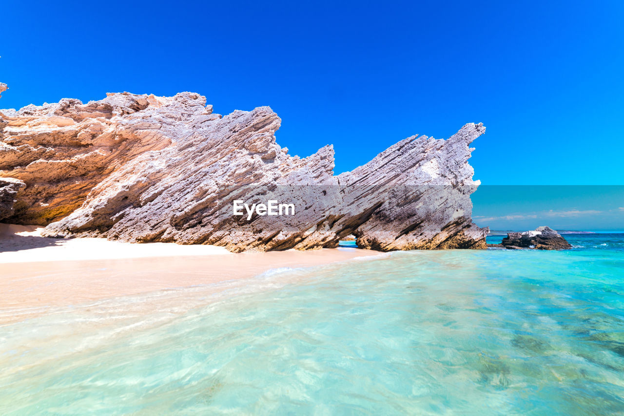 water, sky, sea, beauty in nature, scenics - nature, tranquil scene, tranquility, clear sky, waterfront, rock, rock formation, nature, idyllic, day, land, blue, rock - object, non-urban scene, solid, no people, turquoise colored, outdoors, formation