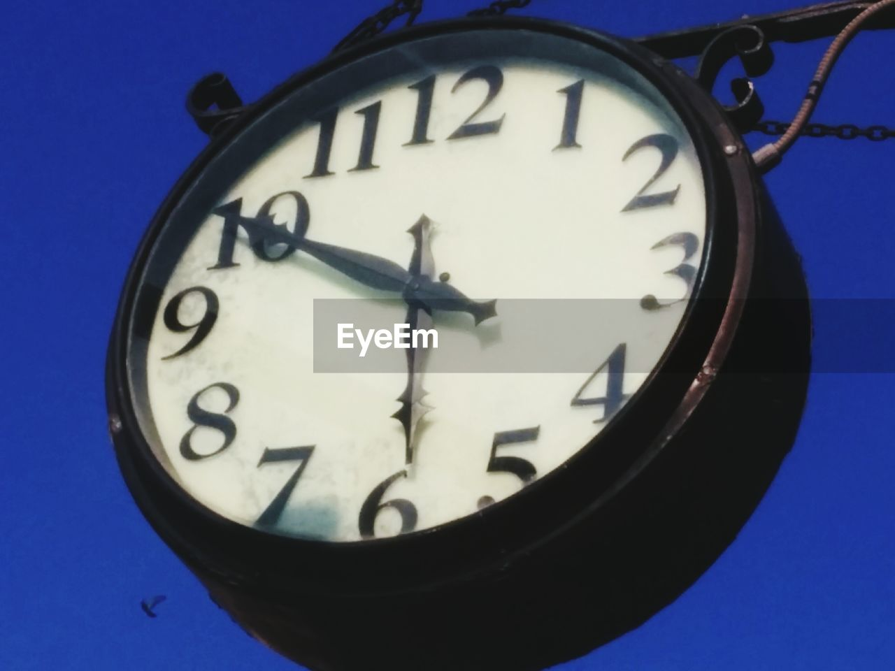 Low angle view of clock against blue sky