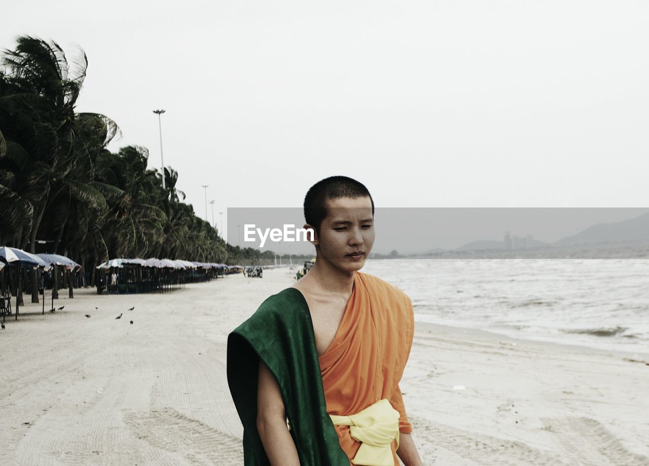Monk Standing At Beach Against Clear Sky