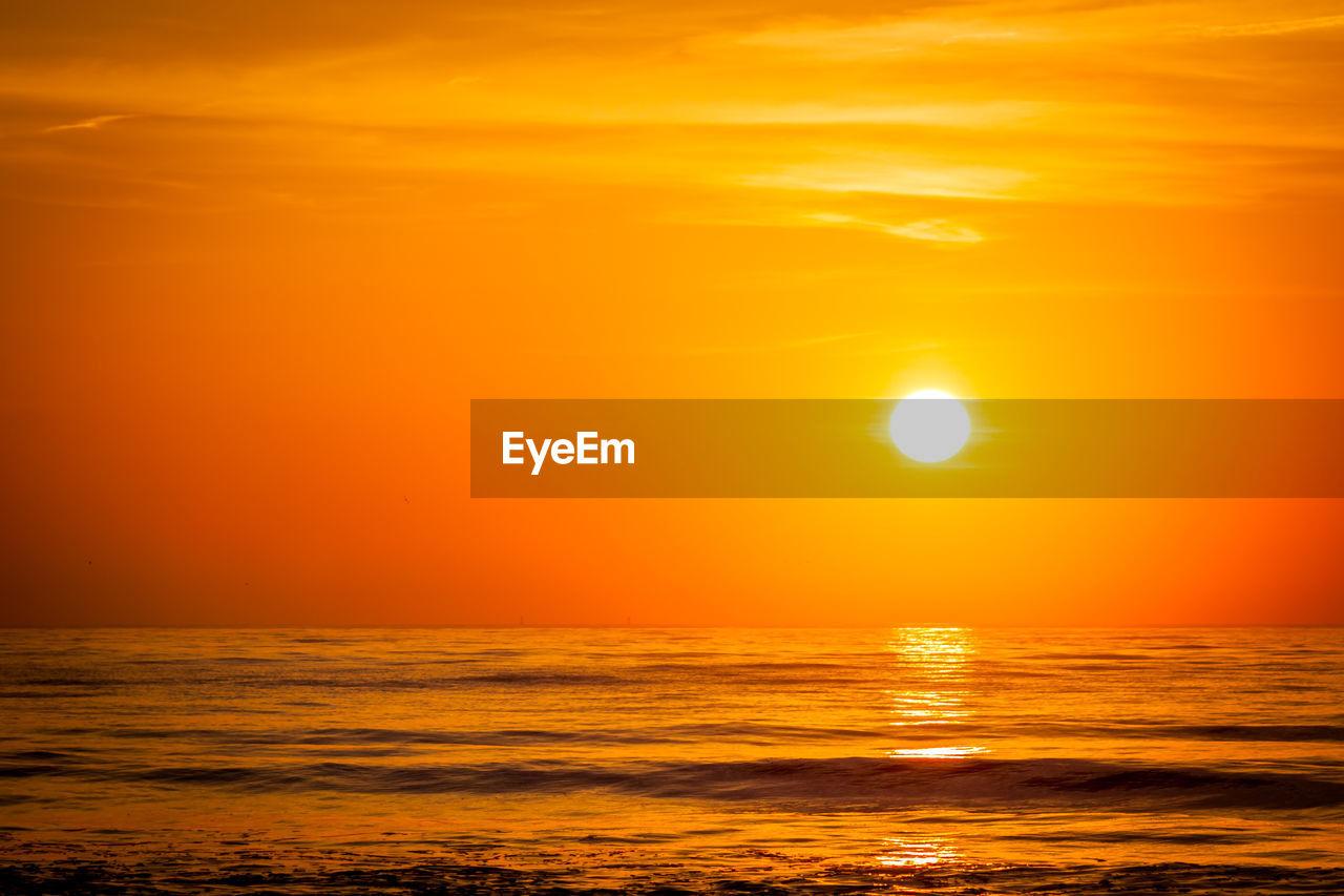 Sun setting over sea