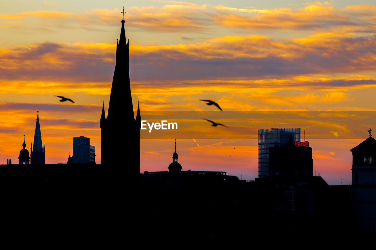 sunset, architecture, orange color, silhouette, built structure, building exterior, sky, city, cloud - sky, flying, bird, skyscraper, no people, beauty in nature, travel destinations, modern, nature, outdoors, cityscape, animal themes