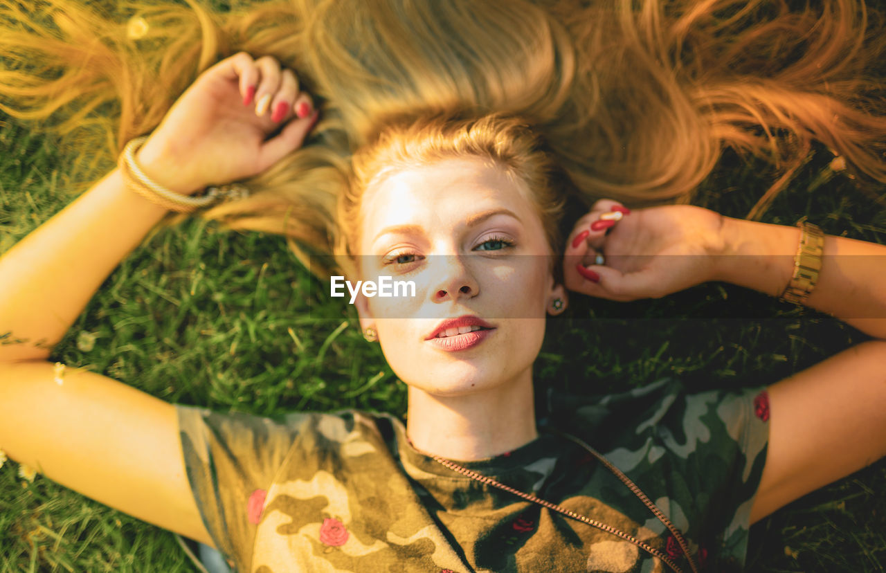 High angle portrait of beautiful young woman lying on grass