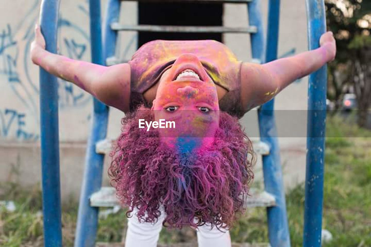 multi colored, fun, happiness, outdoors, front view, focus on foreground, day, looking at camera, smiling, one person, holi, cheerful, people, portrait, children only, close-up, adult