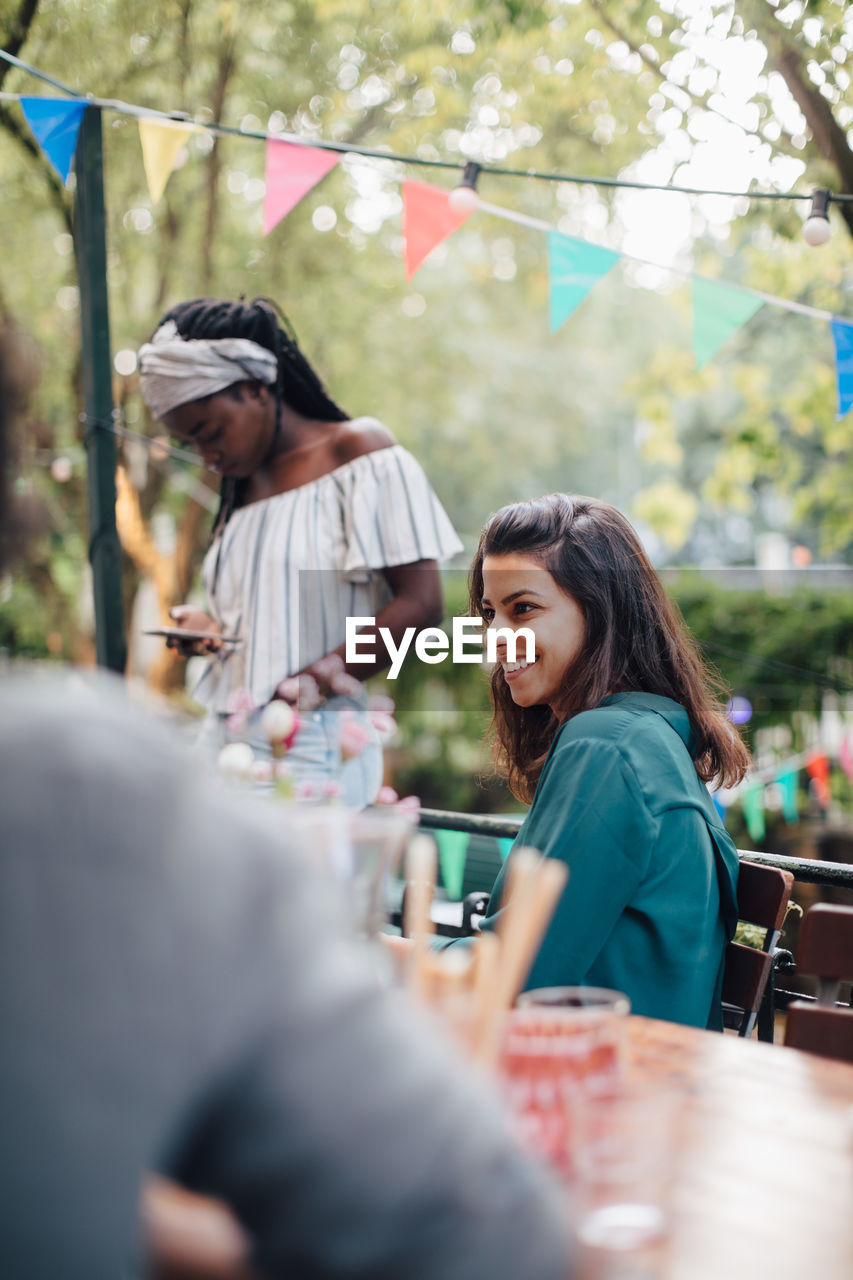 young adult, real people, selective focus, women, food and drink, adult, sitting, happiness, group of people, table, lifestyles, smiling, people, business, young men, casual clothing, young women, emotion, enjoyment, men