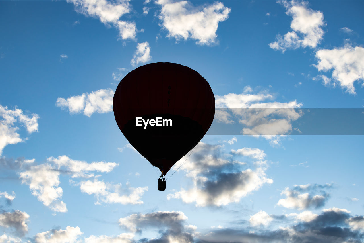 cloud - sky, sky, mid-air, flying, low angle view, transportation, balloon, air vehicle, nature, hot air balloon, day, red, adventure, no people, outdoors, mode of transportation, beauty in nature, freedom, blue, sunlight