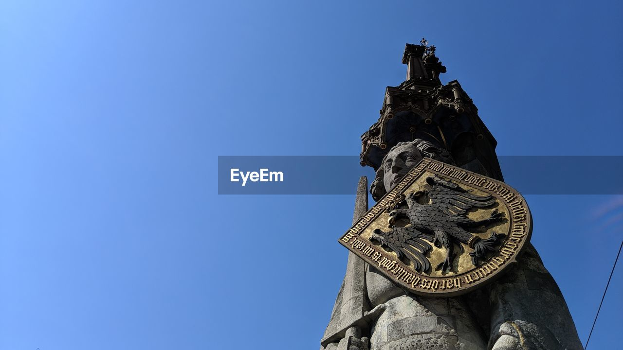 sky, low angle view, sculpture, statue, blue, clear sky, art and craft, representation, human representation, copy space, no people, nature, architecture, day, the past, history, travel destinations, male likeness, creativity, religion, outdoors, clock
