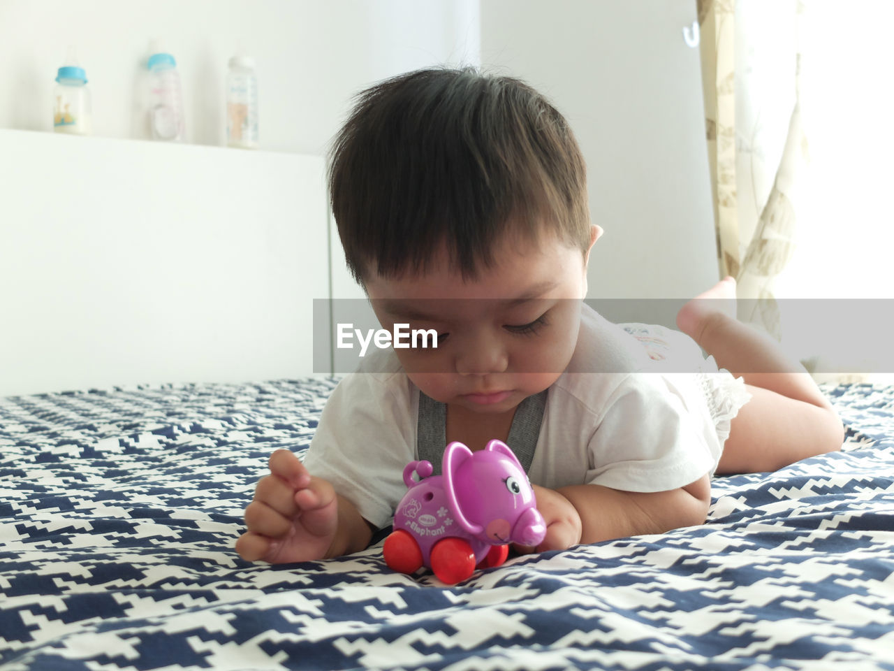 child, real people, one person, childhood, indoors, piggy bank, front view, investment, savings, lifestyles, finance, baby, innocence, bed, home interior, babyhood, young, toddler