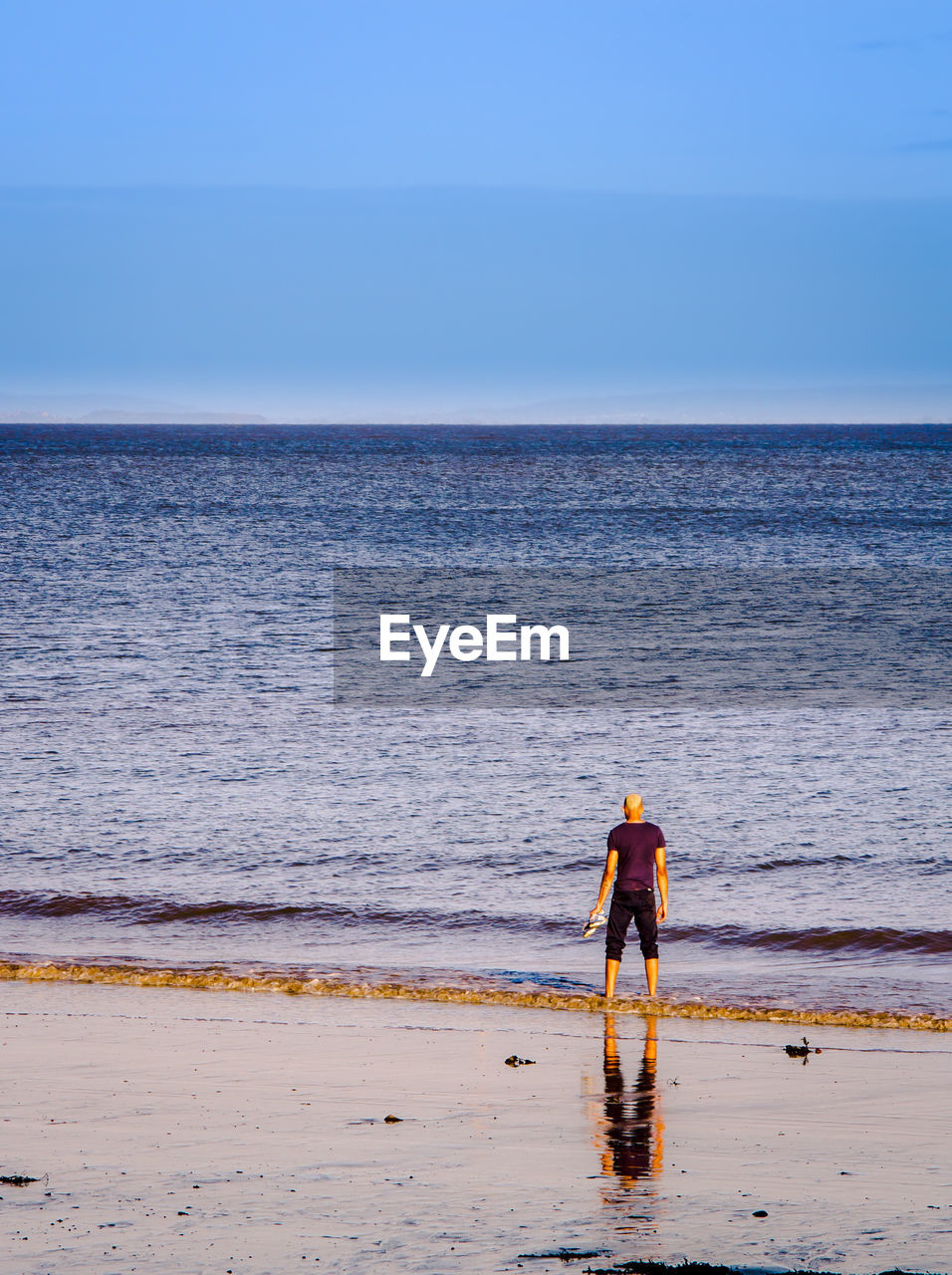 Man Standing On Shore Against Sea At Beach