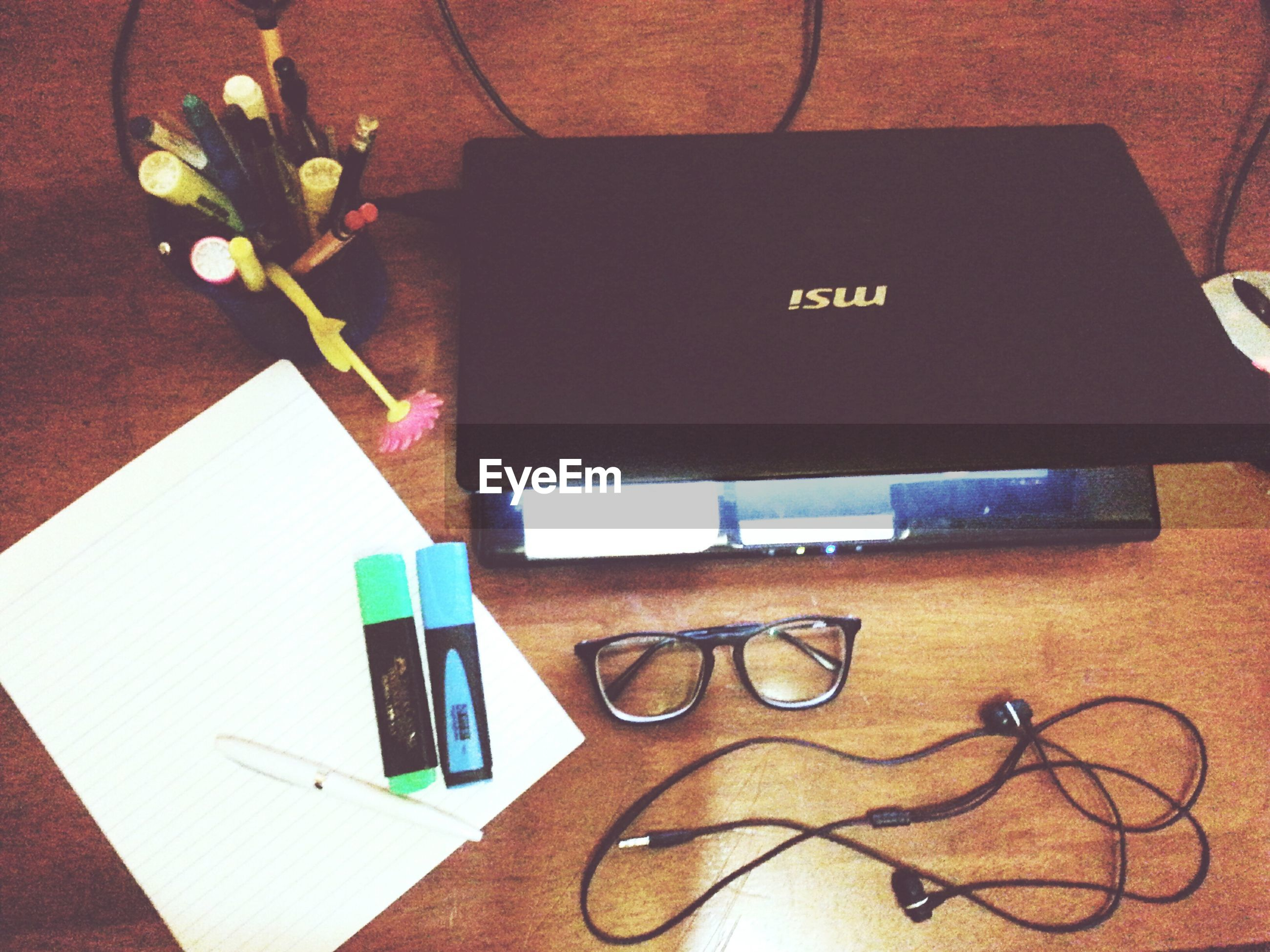 indoors, table, still life, high angle view, communication, paper, close-up, technology, book, connection, wireless technology, text, education, document, home interior, no people, laptop, western script, pen, eyeglasses