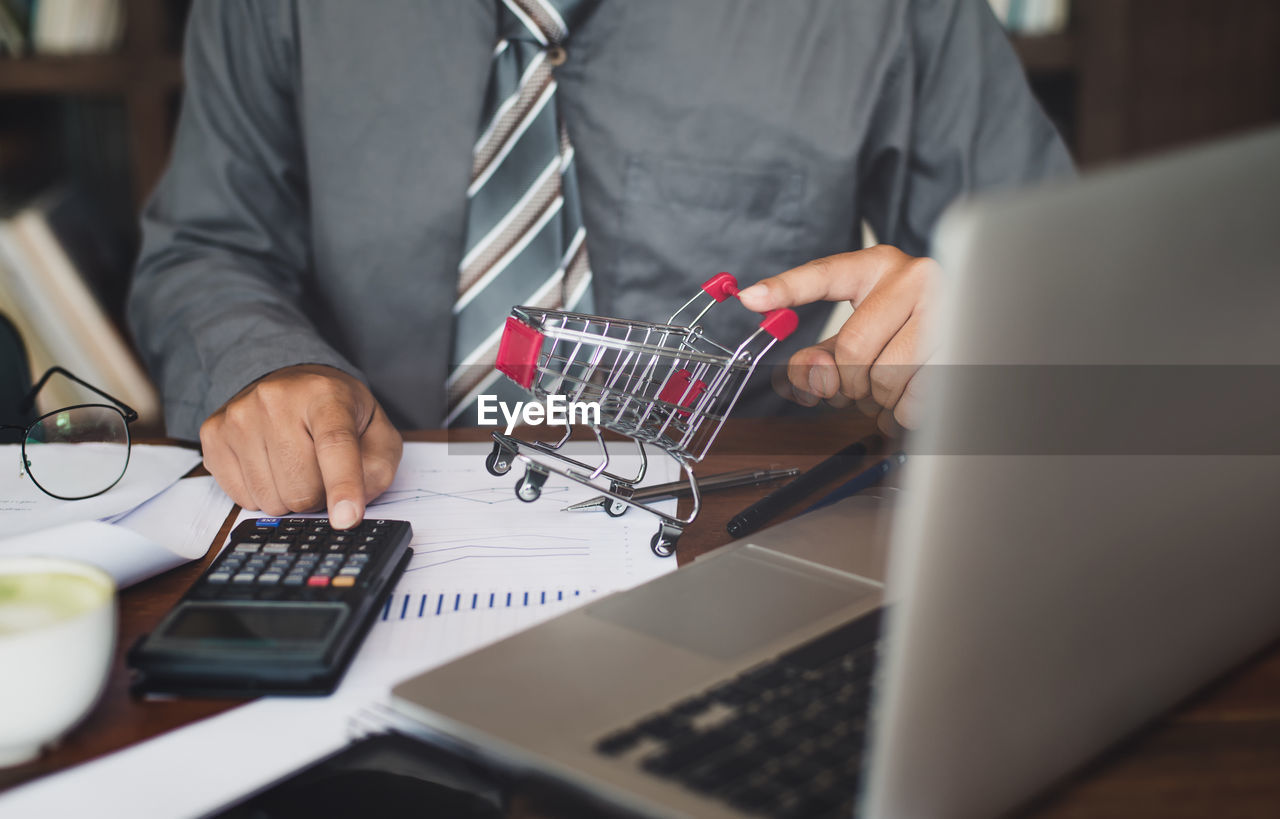 Midsection of businessman calculating at desk in office