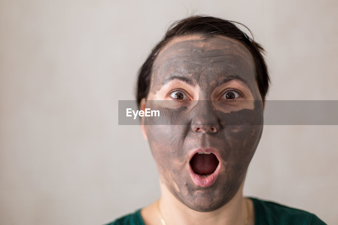 Portrait of shocked woman wearing facial mask against wall