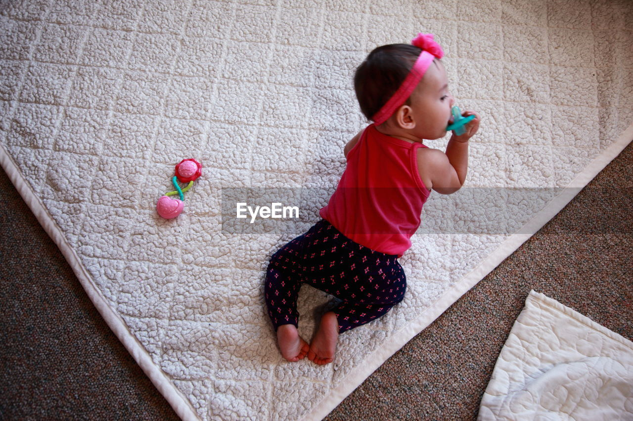 High Angle View Of Baby Girl With Pacifier At Home