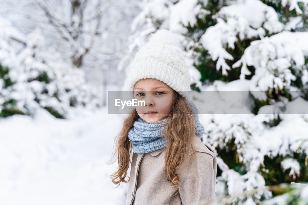 Portrait of girl on snow covered land during winter
