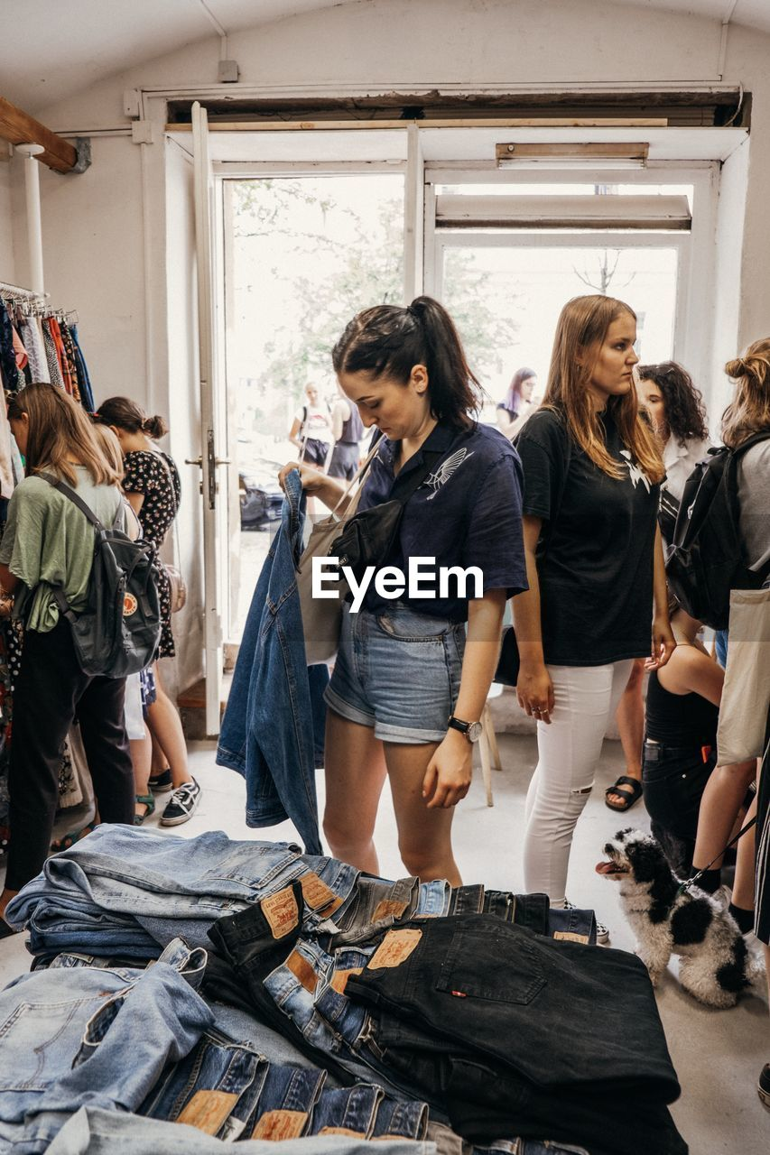 real people, women, casual clothing, young adult, retail, people, lifestyles, group of people, standing, shopping, adult, day, choice, store, indoors, full length, looking, leisure activity, young women, customer, consumerism