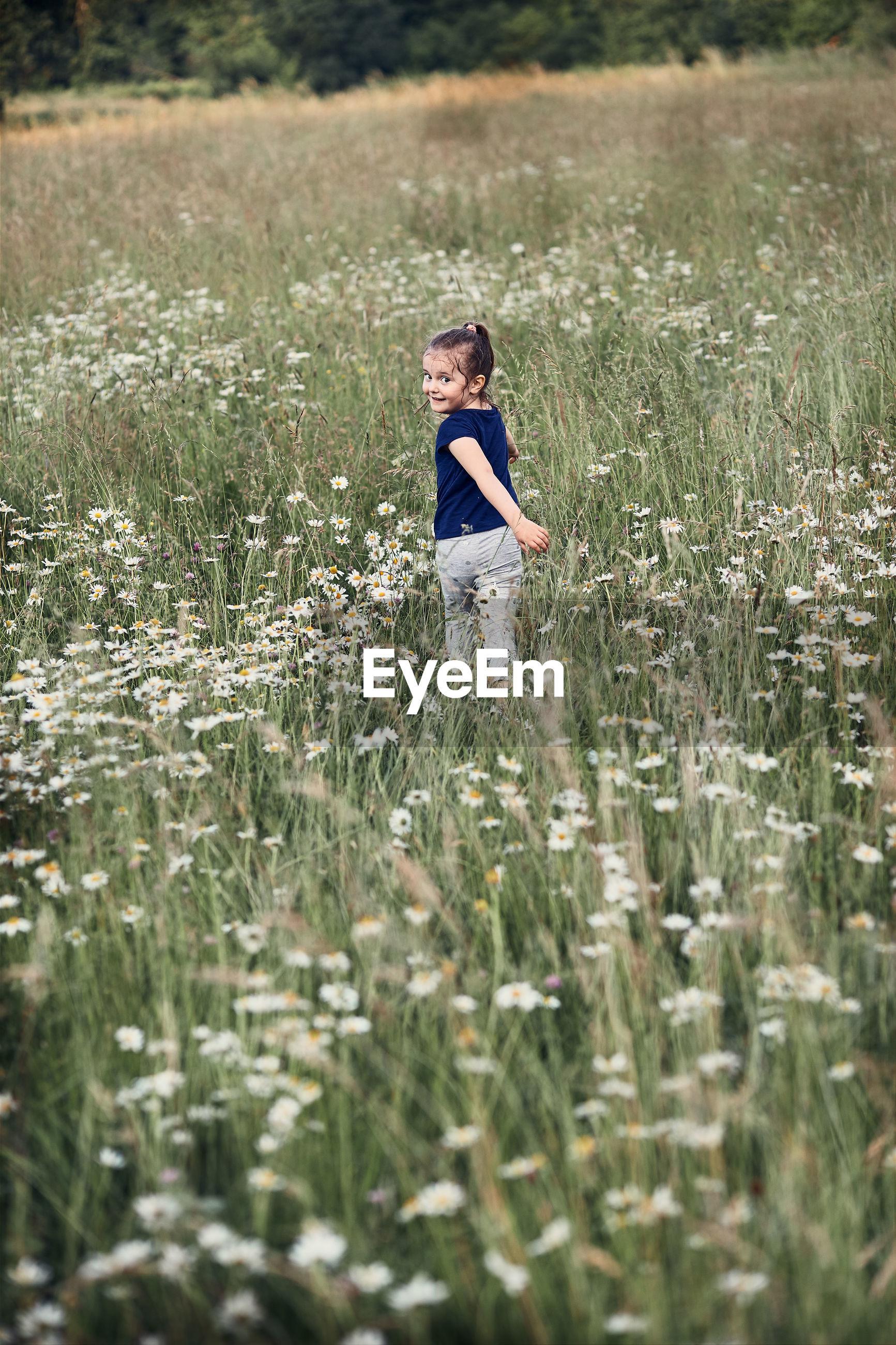 Portrait of smiling girl walking amidst plants on field