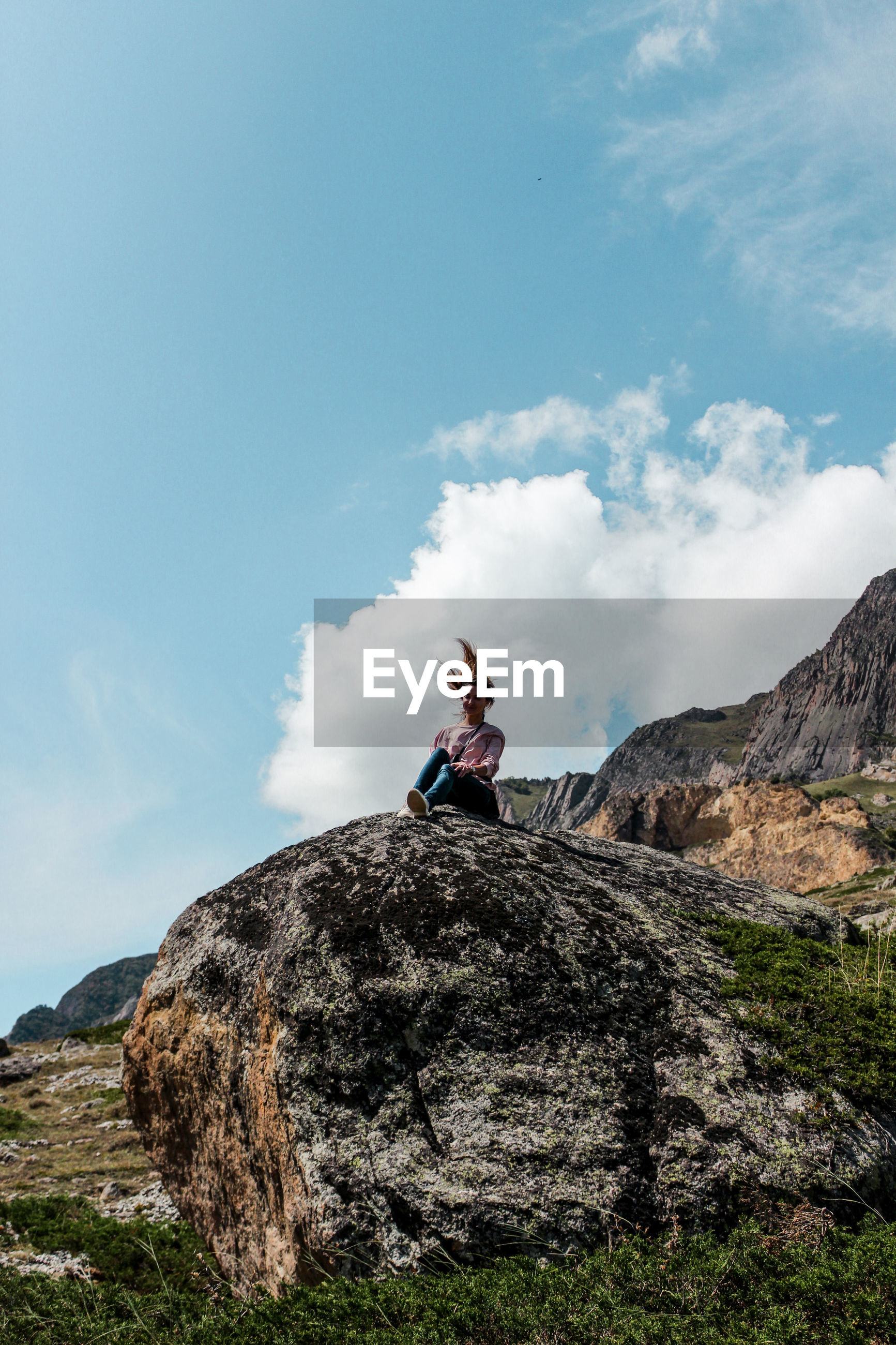Low angle view of woman sitting on mountain against sky
