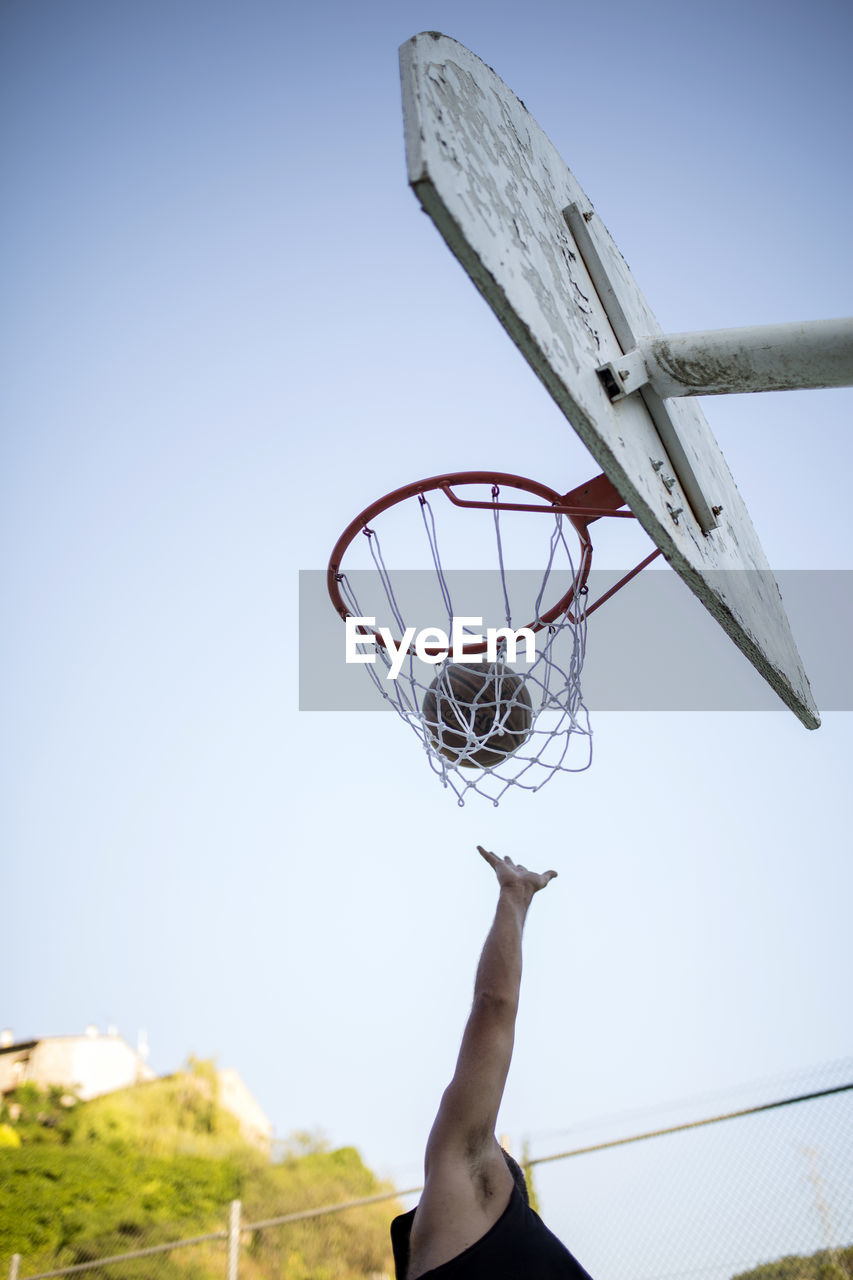 Low angle view of man playing basketball against clear sky