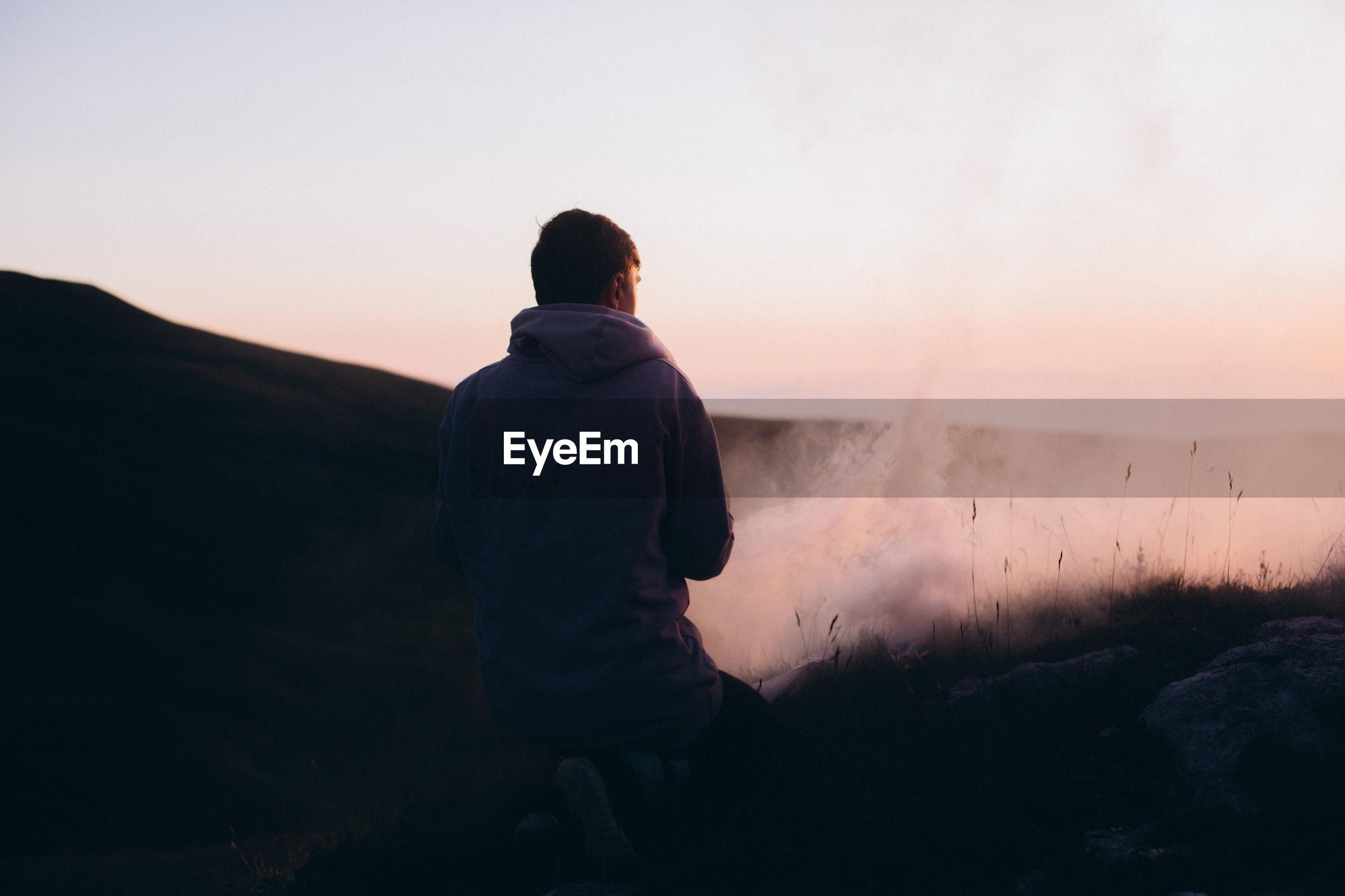 Rear view of man kneeling on mountain during sunset
