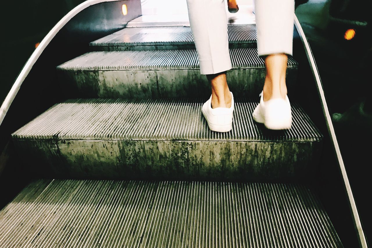 low section, human leg, one person, railing, real people, body part, human body part, shoe, lifestyles, staircase, architecture, standing, steps and staircases, women, transportation, leisure activity, public transportation, metal, escalator, outdoors, human foot, human limb