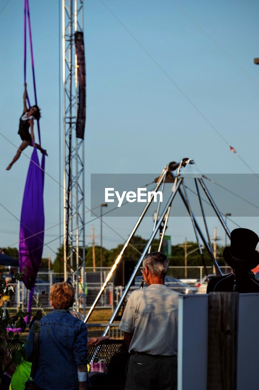 real people, leisure activity, men, lifestyles, women, rear view, arts culture and entertainment, amusement park, clear sky, large group of people, outdoors, sky, togetherness, amusement park ride, day, city, crowd, people