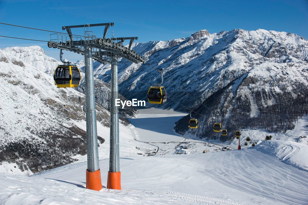 Overhead cable cars on snow covered field