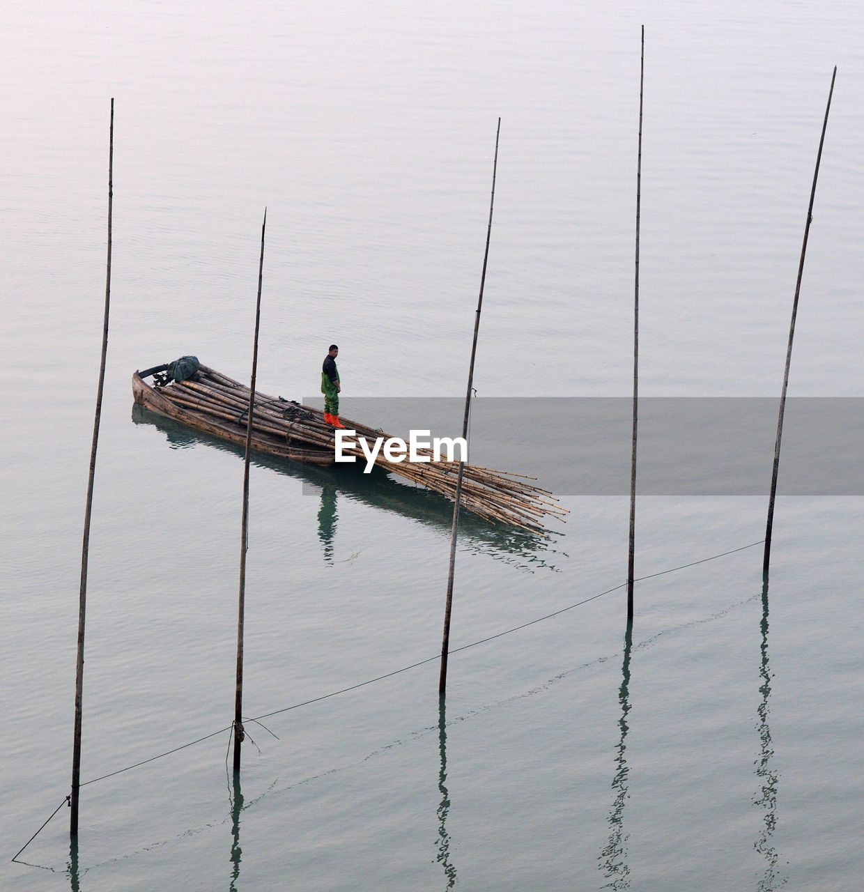High Angle View Of Fisherman Standing On Bamboos In Boat
