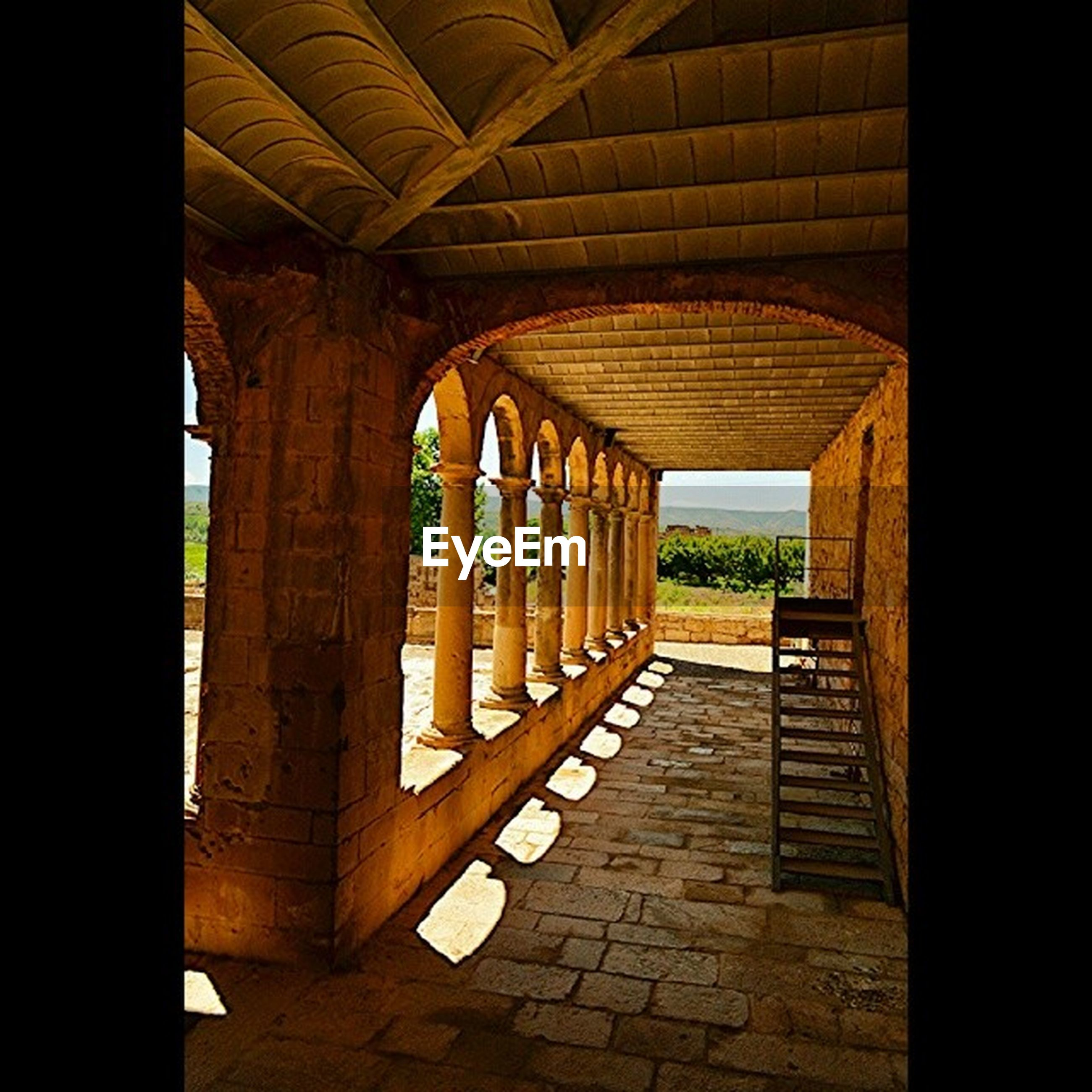 architecture, built structure, indoors, the way forward, arch, corridor, architectural column, history, diminishing perspective, sunlight, colonnade, old, column, archway, day, building exterior, walkway, narrow, no people, vanishing point