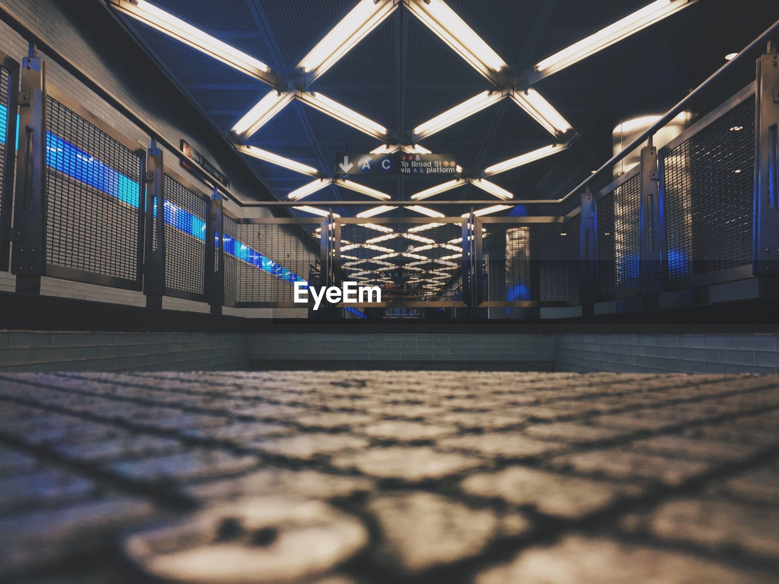 Walkway against illuminated ceiling at subway station