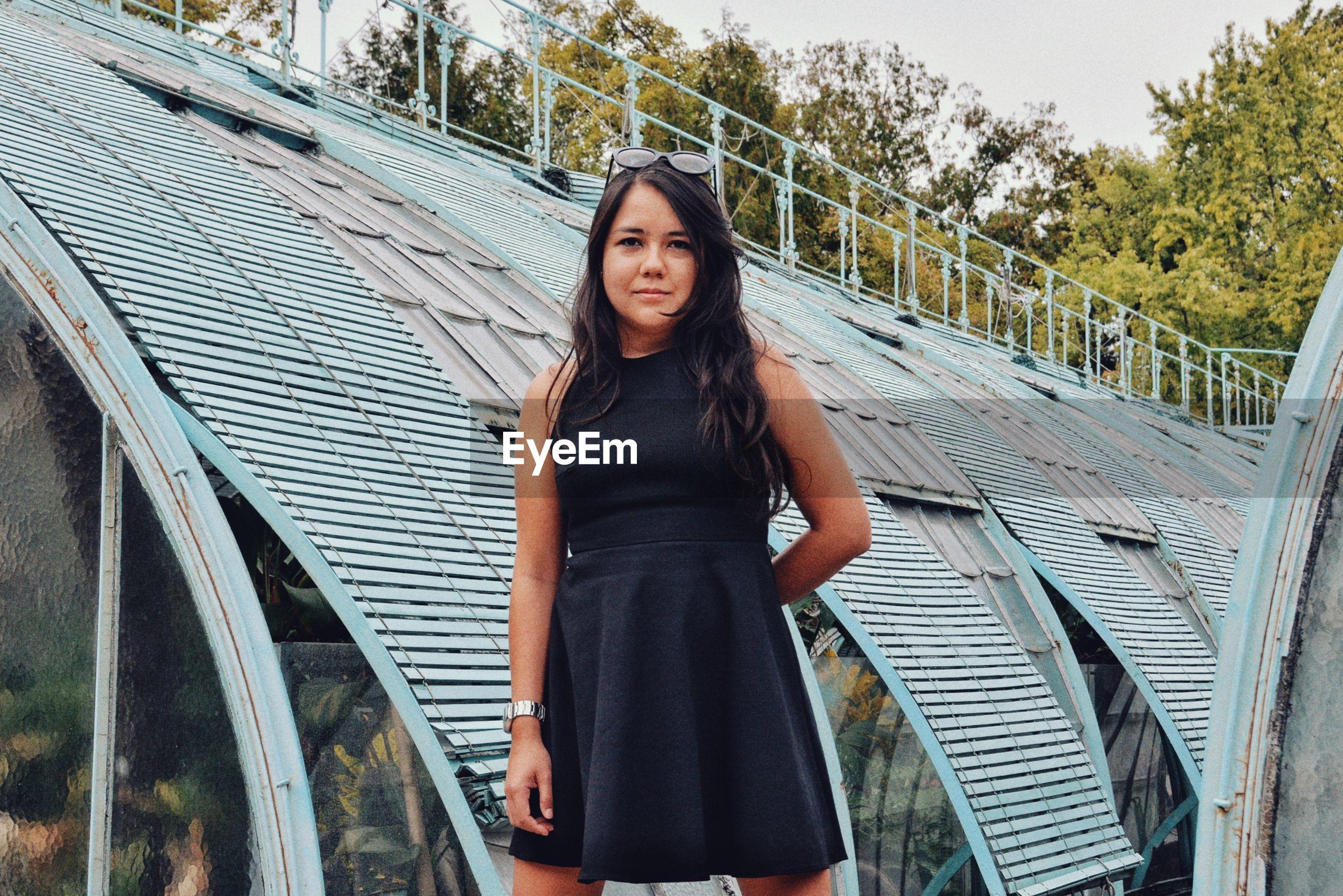 Portrait of beautiful woman standing against bridge