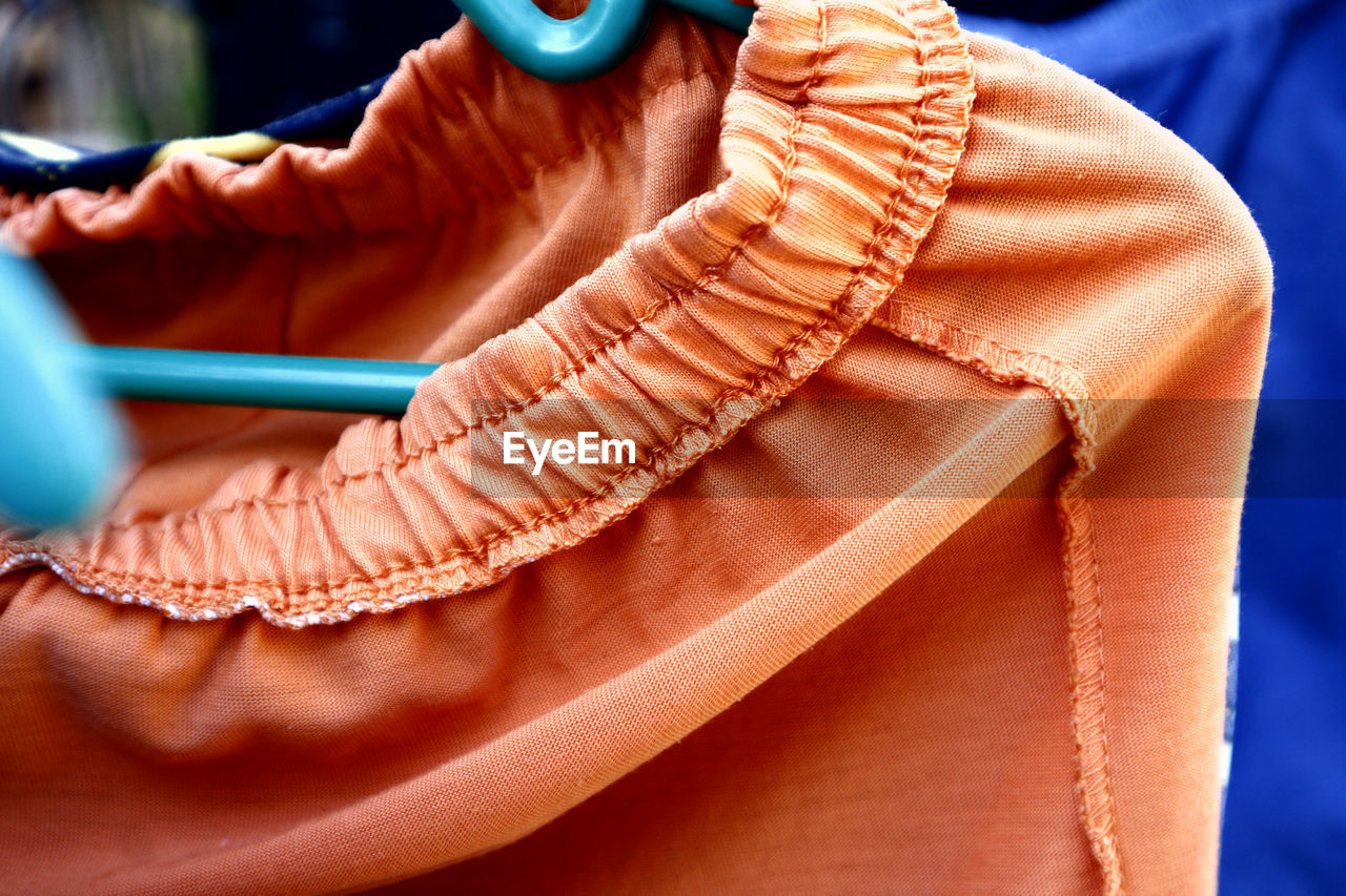 close-up, human body part, one person, clothing, fashion, shoe, indoors, leather, body part, real people, women, lifestyles, adult, orange color, textile, focus on foreground, blue, casual clothing, relaxation