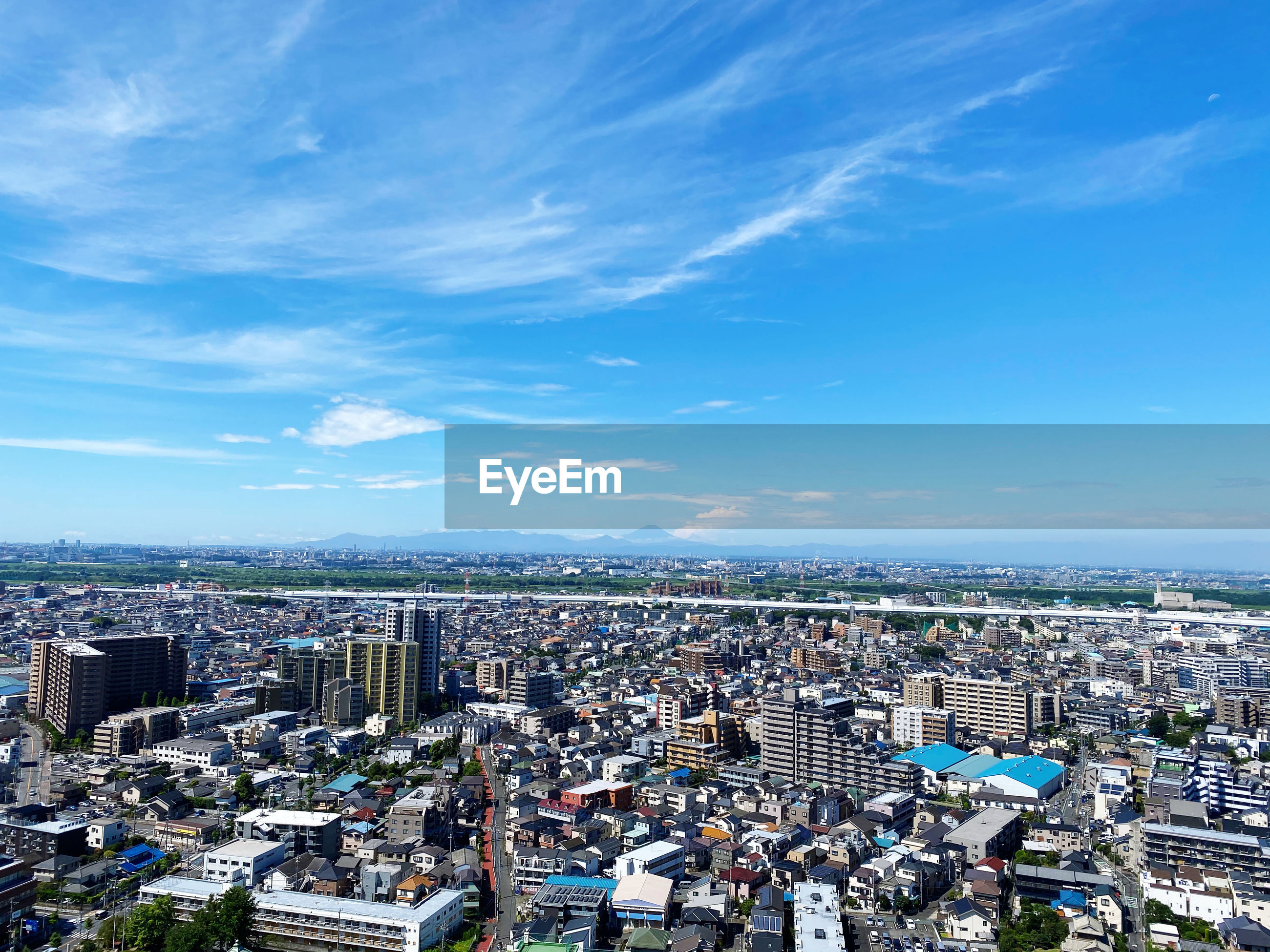 HIGH ANGLE VIEW OF CITY BUILDINGS AGAINST BLUE SKY