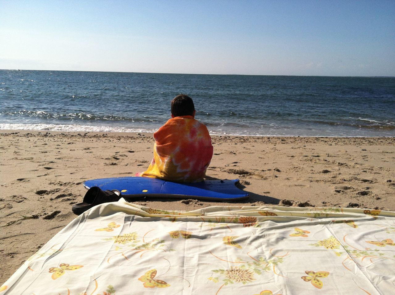 Rear view of boy relaxing at beach against sky on sunny day