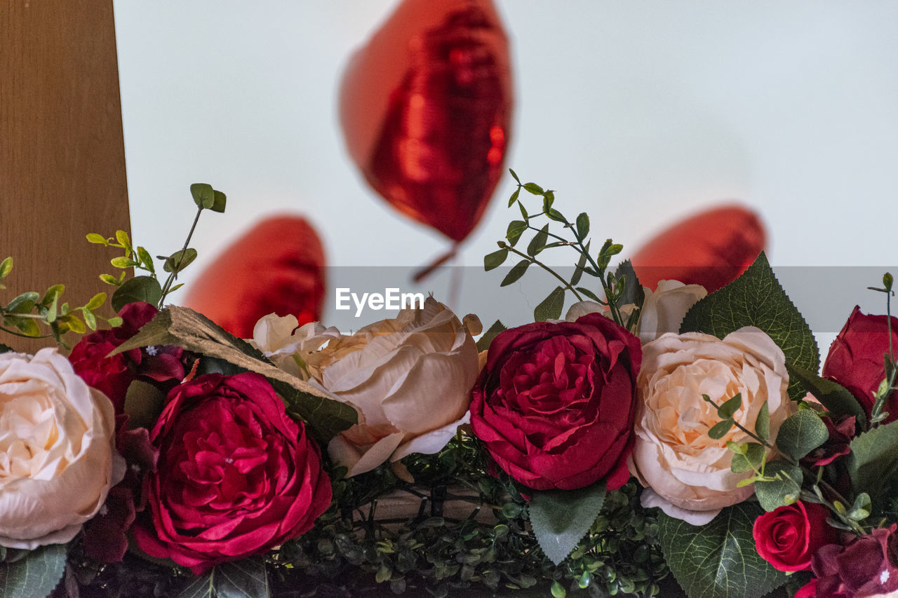 CLOSE-UP OF ROSE BOUQUET ON RED TABLE