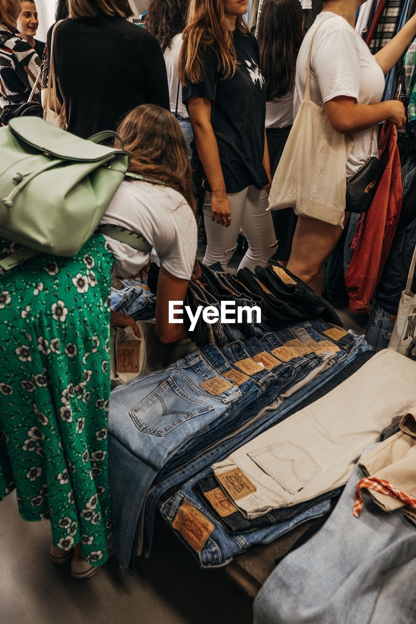 group of people, real people, women, lifestyles, adult, people, leisure activity, casual clothing, rear view, men, medium group of people, standing, group, clothing, day, high angle view, crowd, market, technology, choice