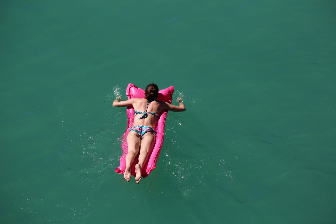 Woman Lying In Float At Calm Sea
