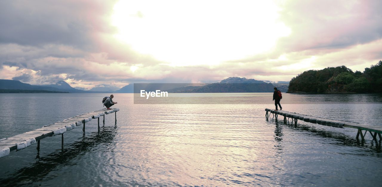 sky, water, scenics, nature, cloud - sky, tranquil scene, tranquility, sunset, beauty in nature, outdoors, one person, sea, real people, day, full length, mountain, men, tree, people