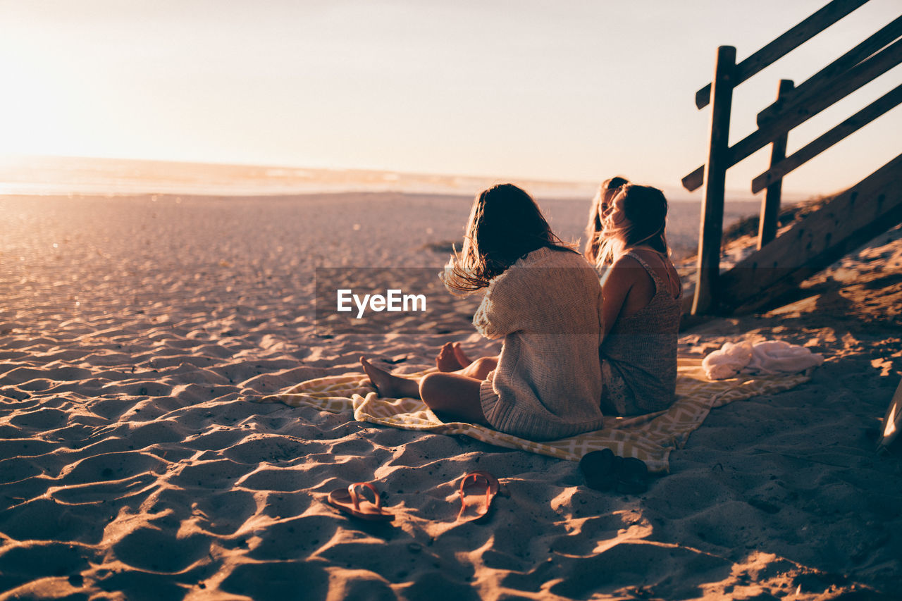 land, lifestyles, sand, two people, leisure activity, beach, real people, sky, sitting, rear view, togetherness, nature, women, relaxation, adult, beauty in nature, people, full length, sunset, scenics - nature, couple - relationship, positive emotion, outdoors