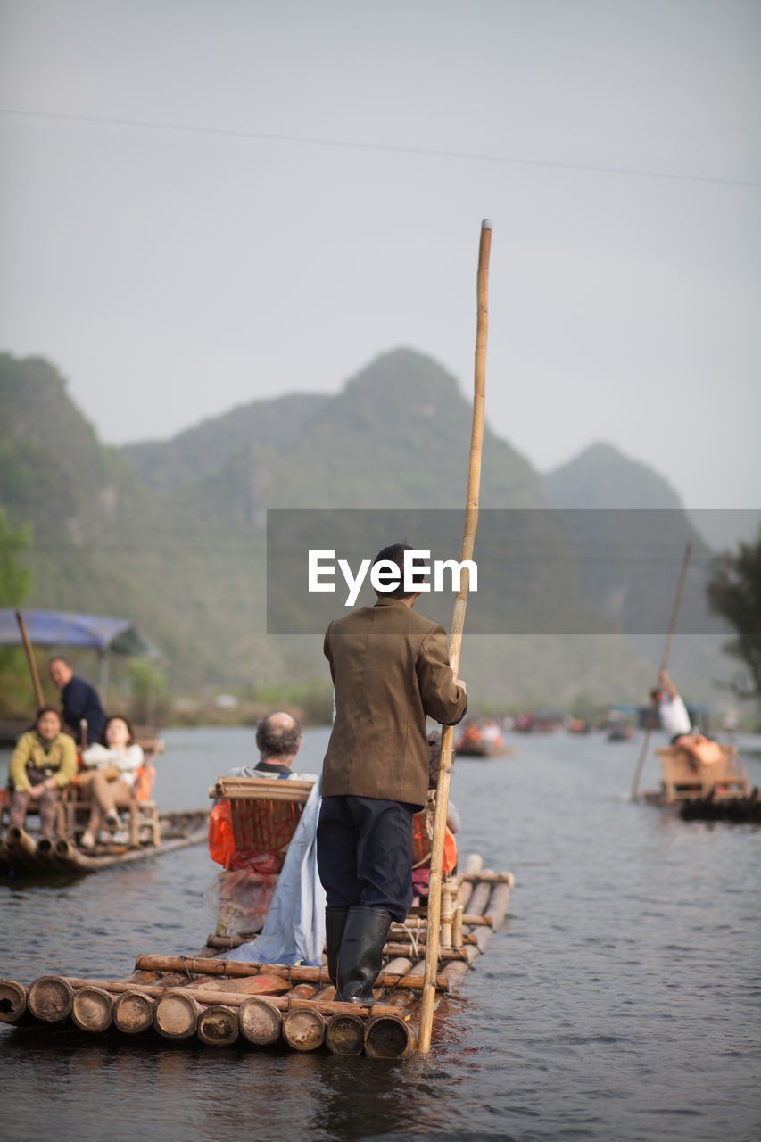People On Wooden Raft Against Mountains