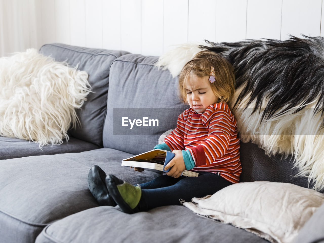 Girl holding book while sitting on sofa at home
