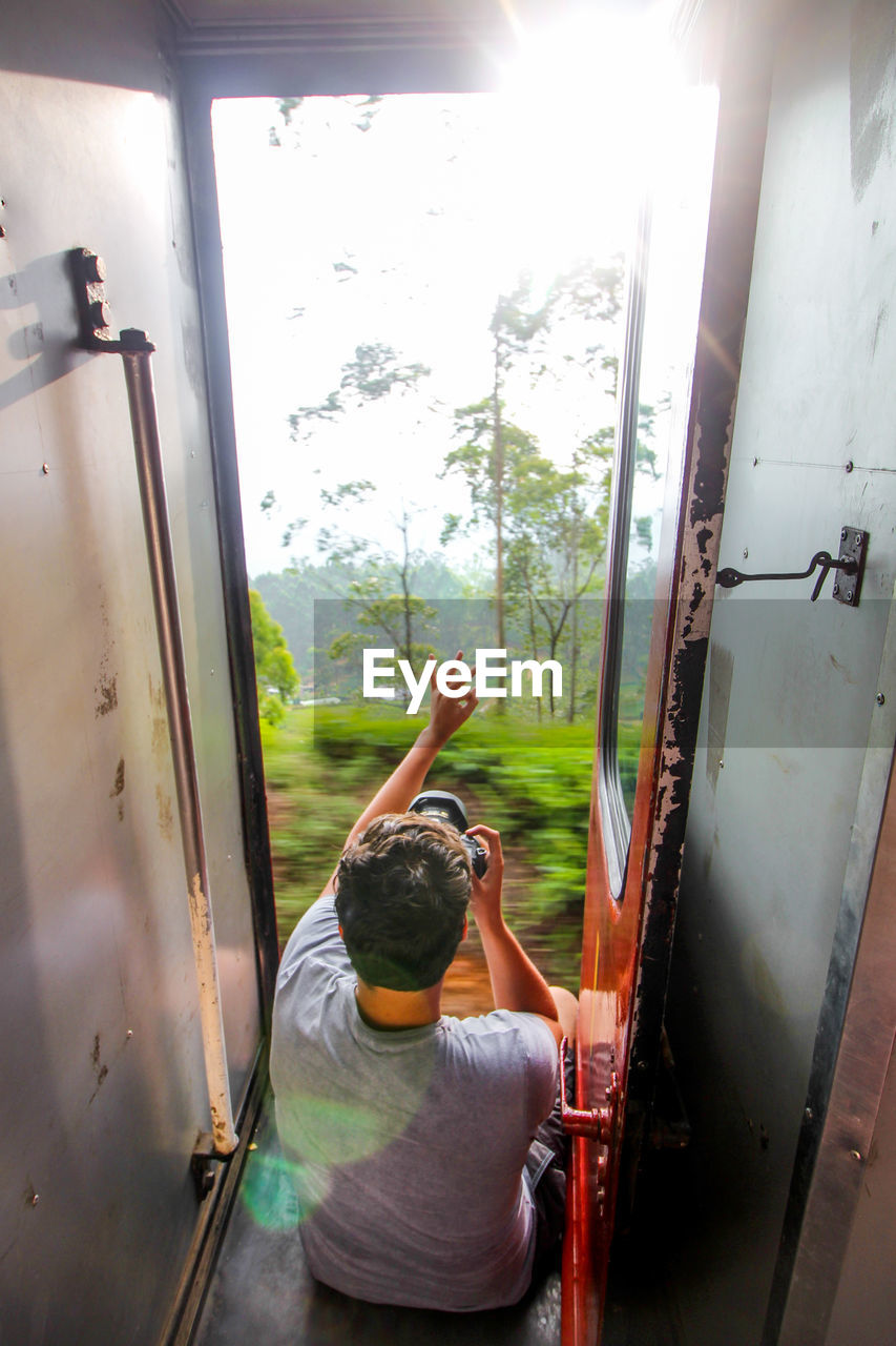 Man Photographing Trees While Sitting In Train