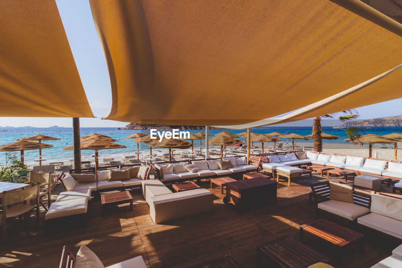 seat, chair, absence, architecture, no people, table, empty, indoors, day, water, restaurant, nature, wood - material, sea, sky, furniture, business, parasol, built structure, sunlight, setting, luxury