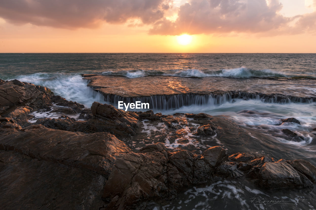 sunset, beauty in nature, sea, nature, water, scenics, sky, horizon over water, tranquil scene, cloud - sky, rock - object, tranquility, idyllic, orange color, no people, motion, wave, outdoors, power in nature, beach, day