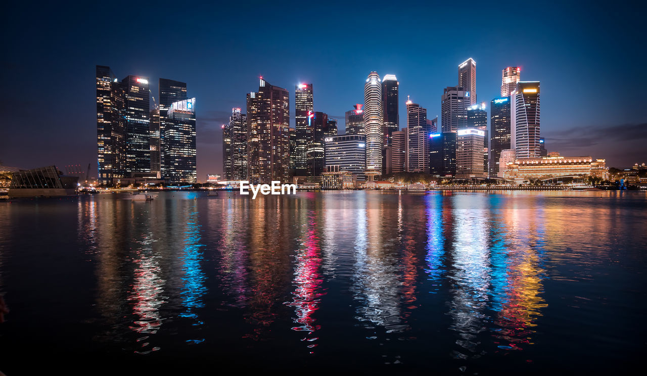 architecture, building exterior, illuminated, built structure, skyscraper, city, night, reflection, travel destinations, modern, waterfront, cityscape, multi colored, no people, water, outdoors, urban skyline, sky