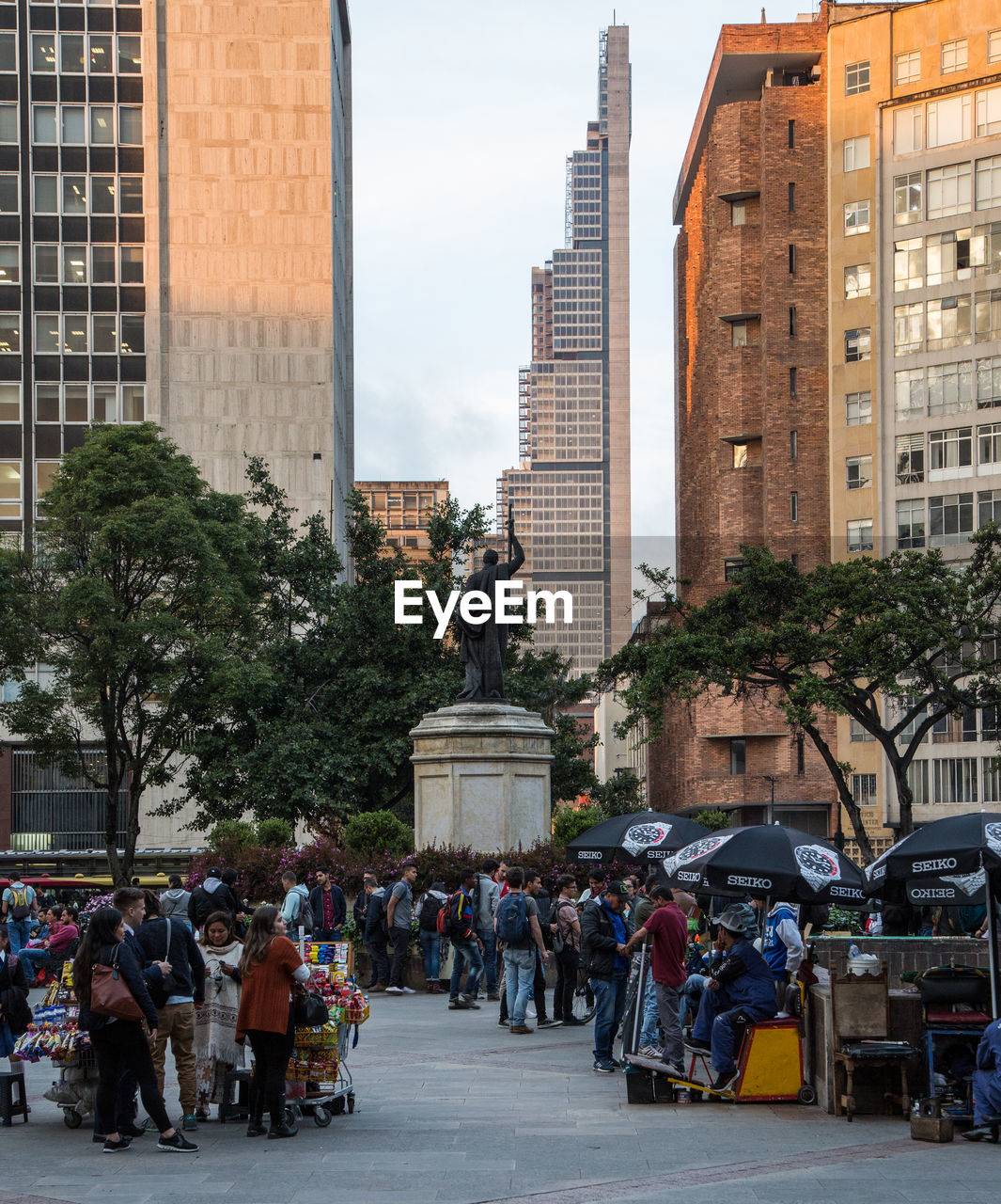 architecture, city, building exterior, group of people, built structure, real people, street, large group of people, men, crowd, city life, statue, transportation, mode of transportation, building, sculpture, women, day, tree, office building exterior, outdoors, skyscraper