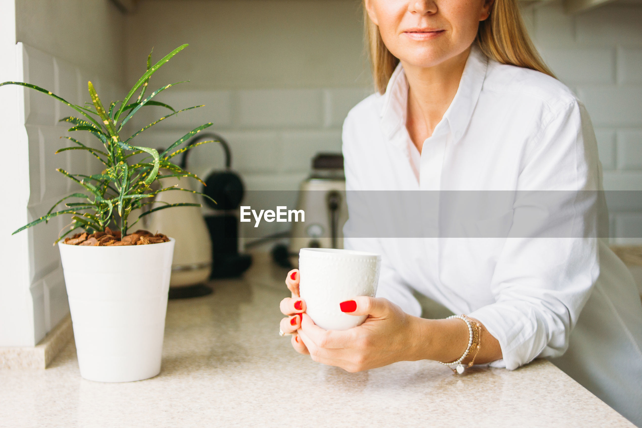 Midsection of woman holding coffee mug on table
