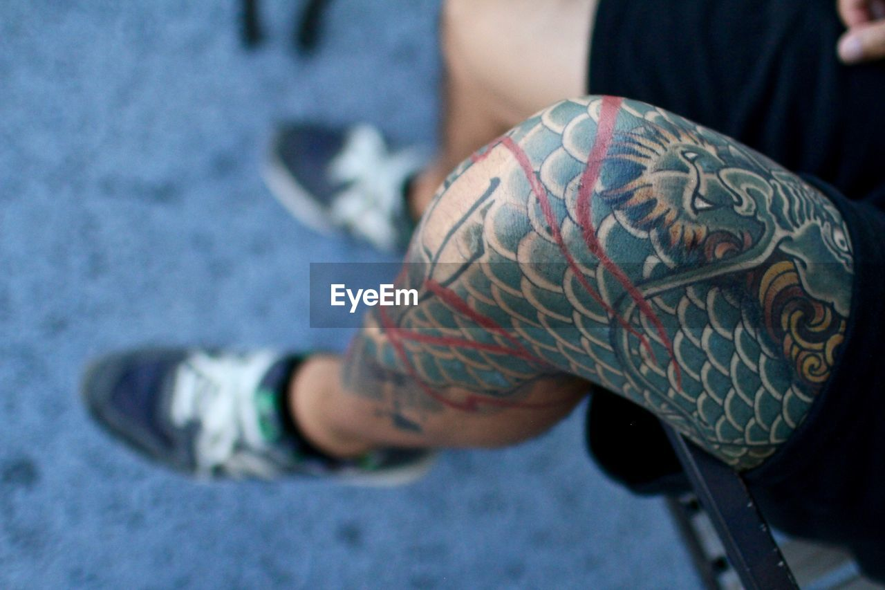 Low Section Of Tattooed Man Sitting On Railing