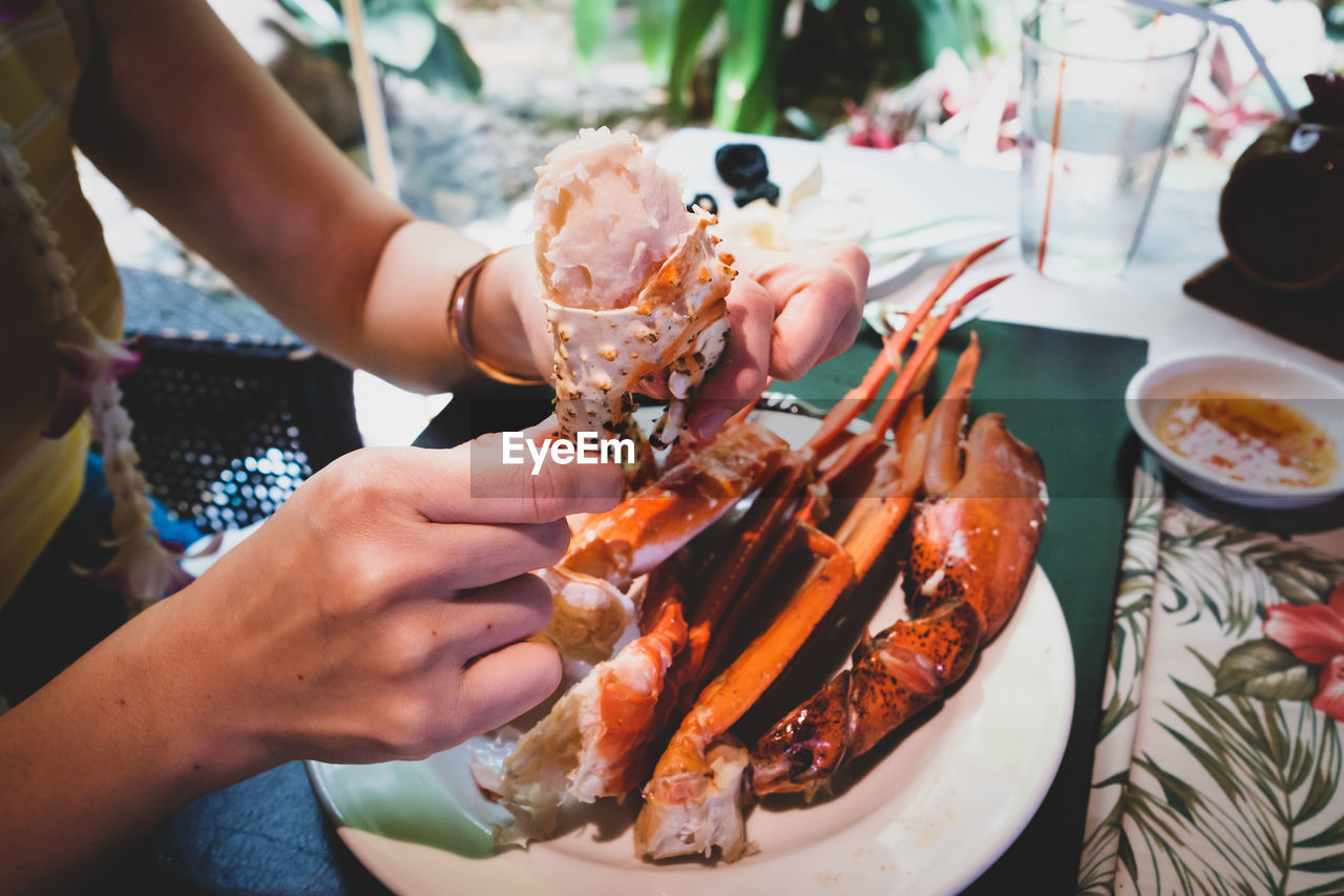 food and drink, food, freshness, real people, plate, human hand, lifestyles, holding, table, human body part, seafood, indoors, hand, healthy eating, ready-to-eat, one person, crustacean, restaurant, wellbeing, finger, glass