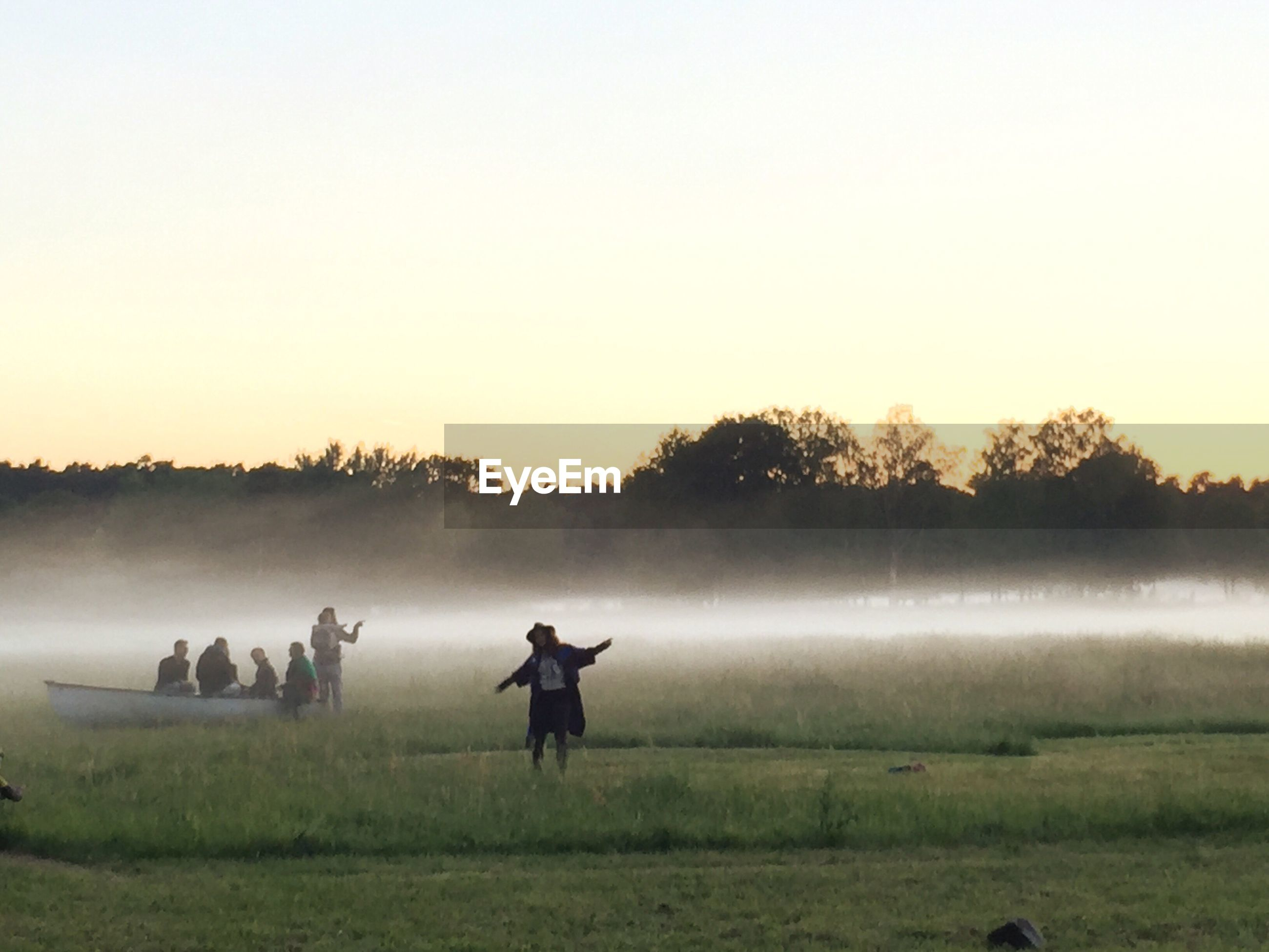 PEOPLE STANDING ON FIELD AGAINST CLEAR SKY