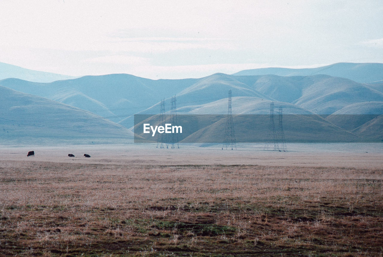 Distant View Of Electricity Pylons On Field By Mountains Against Sky