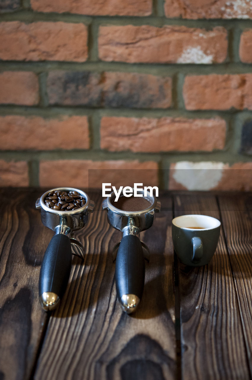 High Angle View Of Coffee In Containers On Table Against Brick Wall At Cafe